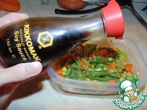 Овощи переложить в форму и перемешать с соевым соусом Kikkoman.
