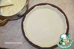 Присыпать стол мукой и раскатать тесто до толщины примерно 3-4 мм. Смазать форму маслом и присыпать мукой. Аккуратно положить будущую основу для чизкейка в форму и прижать по всей поверхности. Сделать бортики.