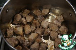В кастрюле с толстым дном разогреть немного масла. Выложить нарезанную кусочками свинину и зарумянить со всех сторон.