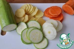 Овощи моем, чистим. Картофель, морковь, лук и цуккини нарезаем (натираем) тонкими кольцами.    Морковь режем более тонкими кольцами, так как она готовится дольше.