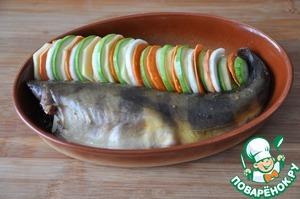 Аккуратно кладём кружочки овощей, чередуя около рыбы, можно положить с обеих сторон от рыбы. Если овощи остались, то кладём их в брюшко рыбы.