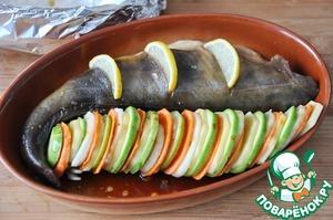 Поливаем овощи оставшимся маринадом.   В рыбе делаем надрезы и вставляем кусочки лимона.    Накрываем рыбу фольгой и ставим в нагретую до 200 градусов духовку на 30 минут.   Далее фольгу снимаем и запекаем ещё около 10 минут.