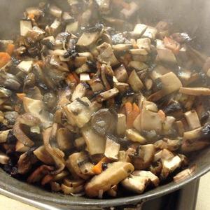 Пока варится бульон готовим зажарку. Грибы промыть, порезать на небольшие кусочки. В большой сковороде нагреть растительное масло, обжарить кубиками нарезанную морковь до золотистого цвета, затем добавить мелко нарезанный лук и жарить до мягкости лука. Теперь сюда добавляем порезанные грибы и жарим пока не испарится почти вся жидкость