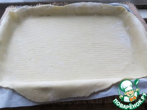 Transfer to a baking sheet /36 26 cm/, covered with parchment, the first layer of dough.  to pierce with a fork the surface.