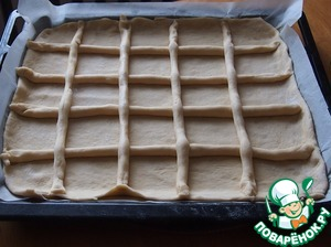 "The dough rose. About a third of put aside, the rest roll out to a thickness of 5 mm and put on a baking tray lined with baking paper. Of the remaining dough make ""sausages"" and place in our reservoir in the form of a lattice. Leave for 20 minutes so that the batter is a little fit."