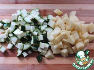 Нарезать кубиками цуккини и картофель,    отправить в кастрюлю с предыдущими овощами.   Добавить горошек и базилик.   Оставить вариться на маленьком огне примерно 30 минут.