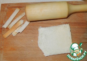 With each piece of bread cut off crusts and roll out with a rolling pin into the reservoir thinner.