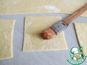 Thinly roll out the dough and cut into squares /10/see 12 /.  each square lubricate the protein.