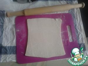 Когда тесто разморозится, аккуратно раскатываем его на слегка припыленной мукой поверхности