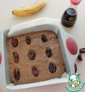 Тесто из замороженных бананов выложить в форму, смазанную маслом или застеленную кулинарной бумагой, сверху вдавить финики. Эта форма 21*21 см.