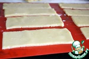 Включаем духовку на 170 градусов.   Достаем тесто из холодильника и раскатываем пласт толщиной 4 мм. Разрезаем на прямоугольники размером 4*12 см. Укладываем на пергамент или силиконовый коврик и выпекаем в разогретой духовке 15 минут.