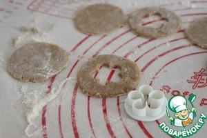 Тесто раскатать максимально тонко. От того, как Вы раскатаете, будет зависеть вкус печенья. Чем тоньше, тем более хрустящими получатся печенья, и наоборот. Стол и скалку припыляем мукой (пшеничной). Стаканом вырезать кружки. Половину кружков оставить целыми, а в остальных с помощью вырубки для печенья в центре сделать отверстия в виде цветочков.