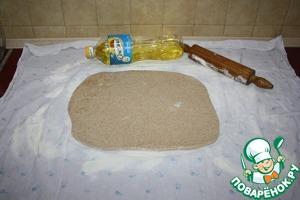 Оставить тесто минут на 30, чтобы оно стало эластичней. Для вытяжного теста используется ткань, чтобы впоследствии удобно было завернуть штрудель. Цельнозерновая мука отстирывается плохо, нужно это учесть. Итак, берем ткань, посыпаем ее мукой (20 г). Выкладываем тесто, смазанное маслом (1,5 ст. л.), слегка раскатываем скалкой.