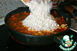 Add carrots, fry. Add rice, mix well, adding salt and seasoning.  Pour boiling water to hide the rice completely.