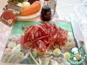 """Режем свинину небольшой соломкой. Ставим плиту на сильный огонь, в сковородку выливаем масло, полностью. Опускаем мясо и жарим примерно минут 10-15 до полной готовности, за пару минут до готовности добавляем в мясо соевый соус """"Kikkoman@."""