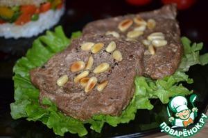 Готовое мясо выкладываем на листья салата и посыпаем обжаренным кедровым орехом.