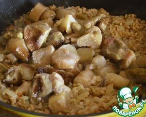 """Мелко режем лук и чеснок. Отправляем на хорошо разогретую сковороду с растительным маслом. Я использую рафинированное растительное масло """"Олейна"""".   Припускаем до прозрачности в течение 3-х минут.   Добавляем в сковороду сливочное масло и перловку. Продолжаем помешивать и жарить крупу до прозрачности. Добавляем размороженные белые грибы! Выпариваем всю жидкость."""
