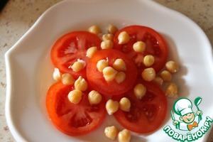 Выкладываем на тарелку кольца помидоров, сверху посыпаем нутом, солим, перчим.