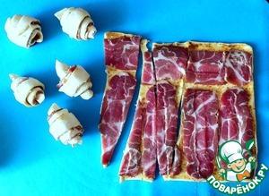 Поверх выложить ломтики сыровяленого мяса. Разрезать тесто вместе с начинкой на треугольники и свернуть рогалики.