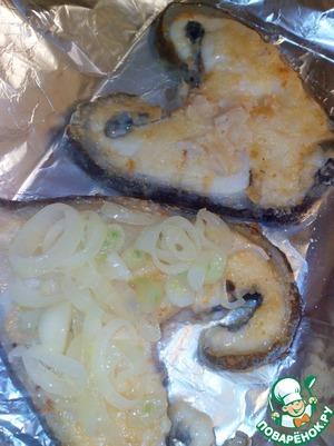 Духовку разогреть до 200 гр.   Противень застелить фольгой, смазанной растительным маслом.    Выложить рыбу, затем лук. Слегка посолить.