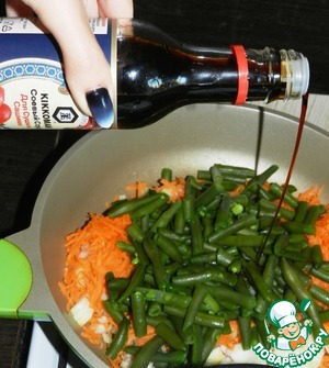 Лук, морковь очистить.    Морковь натереть на тёрке, лук мелко нарезать.    Обжарить в небольшом количестве растительного масла вместе с фасолью. Полить по поверхности соусом Kikkoman и посыпать семенами калинджи или другими специями по вкусу.