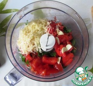 In the bowl of a blender put the Basil, tomatoes, pine nuts, grated Parmesan, sliced garlic