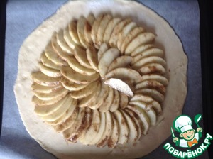 Preheat the oven to 190 degrees.  Baking tray lay a parchment or silicone Mat.  On a lightly floured surface roll out the dough into a circle with a diameter of about 25-30 cm to Transfer the dough on a baking sheet.  On the dough evenly lay out slices of apples, not reaching the edges of 5-6 cm.
