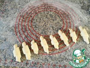 Для сладкоежек можно посыпать тесто сахаром, молотыми орехами и т. д. Закрутить рогалики от широкой стороны к центру.      Сейчас, в сыром виде, рогалики немного отличаются друг от друга, потому что закручивать их можно более или менее плотно, но после духовки они значительно увеличатся в объеме и будут практически одинаковы.