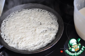 Heated pan (preferably pancake) lubricating oil, pour a ladle of dough, distribute it over the surface of the pan. Bake on medium heat (I have 4-5 of 6). As soon as the dough will change color, flip the pancake.  Bake for about a minute on the reverse side. Remove the finished pancake on a plate.  When baking periodically grease the pan with oil.