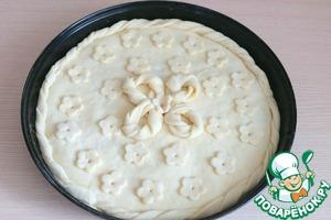 Край пирога смазать водой, выложить жгутики из теста по краю пирога. Оформить пирог по вкусу.