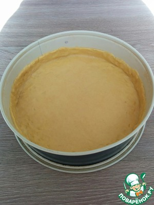 Take the dough from the refrigerator and distribute in a baking dish with a thin layer, make a small bumpers. I have a form with a diameter of 24.5 cm.