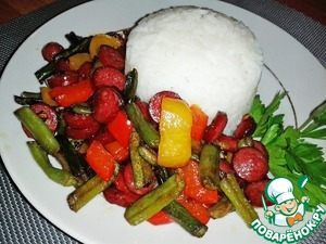 Spread on a plate of rice and sausage with vegetables.