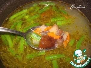 В кастрюлю, где будет вариться суп, вскипятить 800 мл воды, всыпать нарезанную стручковую фасоль (если из заморозки, то не размораживая), добавить овощную зажарку, грибной соус, сушеный тимьян, соль, молотый перец. После закипания варить 5 минут.