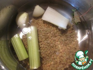One stalk of celery chopped coarsely, put in a pot ( volume 3 l ), there also add peeled onion, thyme and Bay leaf, tied with string. Cover with cold water, add the lentils, bring to a boil and cook until the lentils are tender.