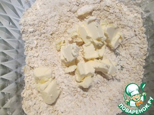 В миске смешиваем овсянку, муку, соль и перец. Добавляем сливочное масло. порезанное кубиками, перетираем в крошку.