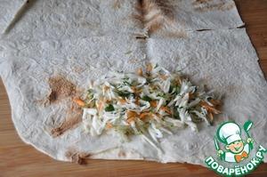 Лист лаваша перерезаем пополам.   Посредине с краю кладём капустный салат.