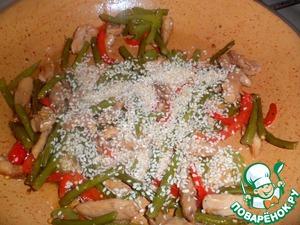 Как только стрелки станут оливкового цвета, добавить кунжут и дать слегка поджариться, помешивая.