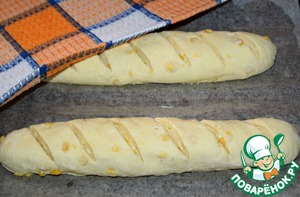 Put the loaves on a baking sheet, the laid parchment. Parchment oil. To make the billet cuts. Cover with a towel and leave for proofing in a warm place for 20-25 minutes.