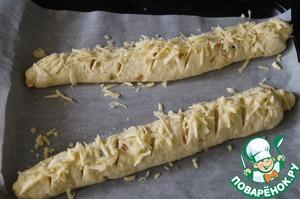На багетах сделать надрезы, сбрызнуть его водой и посыпать тертым сыром. Выпекать в разогретой до 180-190 градусов духовке, до румяной корочки.