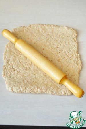 На смазанном маслом столе обомните тесто и раскатайте его толщиной около 0,5 см