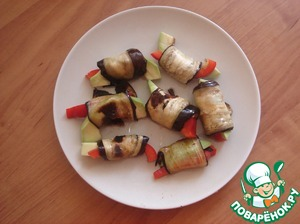 Twisted rolls are healthy and tasty. On the edge of the slices of eggplant spread, avocado and bell peppers, wrapped.