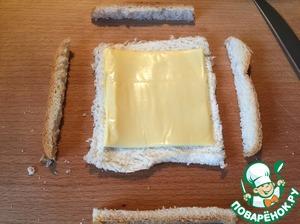 У каждого куска хлеба отрезать корки со всех сторон, раскатать мякоть скалкой, положить сверху сыр.