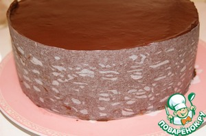 Gently wrap the ribbon around the cake and press firmly. Place cake in refrigerator and allow the chocolate to harden and then carefully remove the paper.