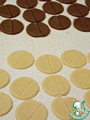 Раскатать обе части теста в пласты толщиной 0,5 см. Рюмкой или выемкой вырезать круги и разрезать из пополам.