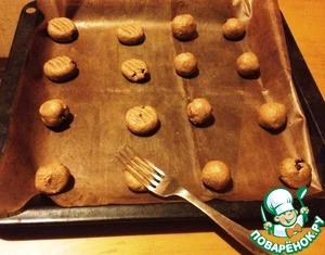 От теста отщипнуть кусочек величиной с грецкий орех, скатать шарик и выложить на противень, покрытый ковриком для выпечки. Немного прижать сверху обратной стороной вилки.   Поставить в разогретую духовку. Выпекать при 200С примерно 25 минут