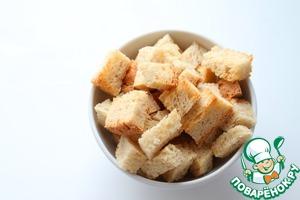 Батон нарезать кубиками, выложить на противень. Сбрызнуть 1 ч. л. оливкового масла, солью и гранулированным чесноком. Запечь при 180 градусах до золотистого цвета (минут 5).