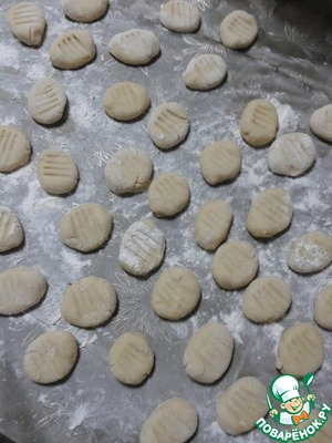 Divide the dough into 3-4 parts and each roll with a long sausage. Cut into pieces with a width of approximately 2 cm. Roll each piece oval balls and with a fork slightly flatten, so you can see stripes that are typical of such dumpling.