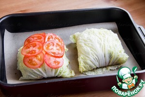 Lay out the envelopes with the fish in the parchment or baking paper. Thinly slice fresh tomatoes and lay on top of each cabbage envelope, a little salt
