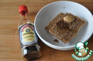 Берём чёрный хлеб, можно подсохший, отрезаем корочку, поливаем оливковым маслом, соевым соусом и острой горчицей. Я выбрала соевый соус ТМ Kikkoman.
