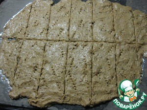 Now with wet hands dough on the surface of the baking tray to a thickness of about 2-3 mm, make nakoly with a fork and a knife to define the boundaries of our bread, but not cutting through to the end.